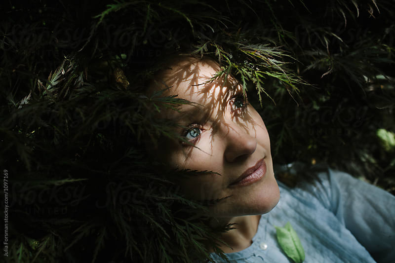 Portrait of a woman resting in nature. by Julia Forsman for Stocksy United