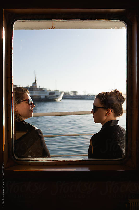 Two women in conversation as they travel by boat. by Julia Forsman for Stocksy United