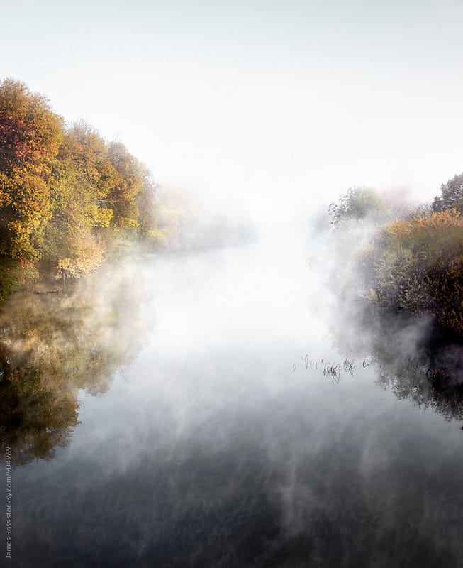 Misty river with autumnal trees by James Ross for Stocksy United