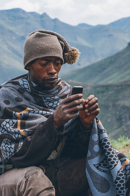 Rural African Basotho herdsman using a mobile phone by Micky Wiswedel for Stocksy United