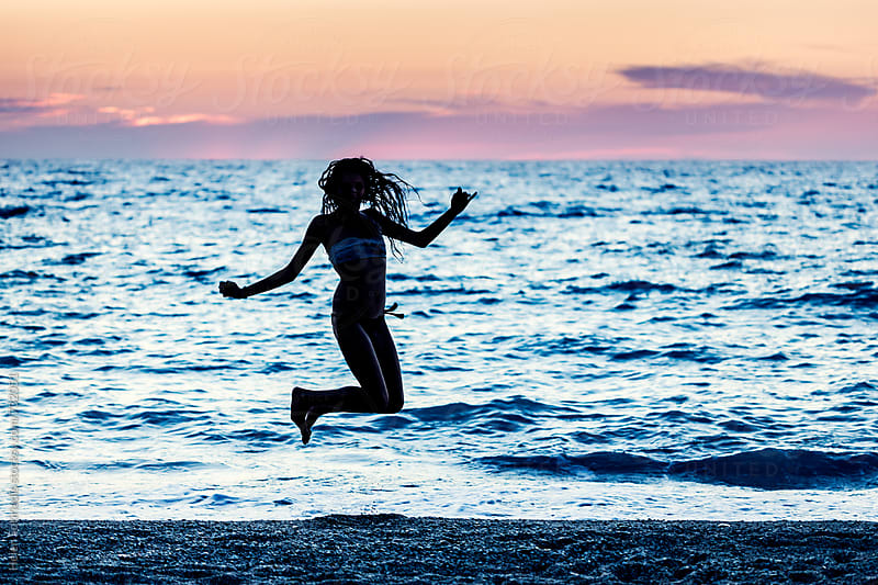 Young Woman Jumps at Twilight on the Beach by Helen Sotiriadis for Stocksy United