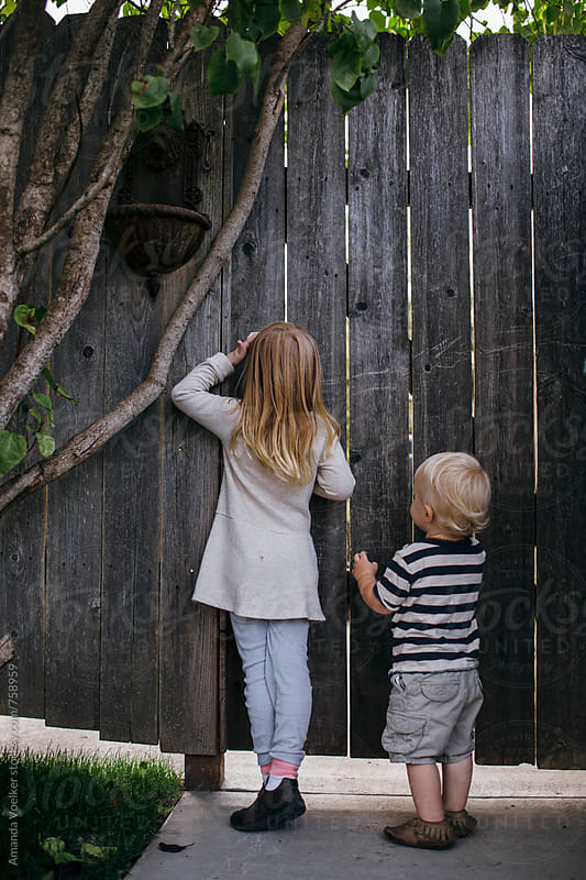 A Young Sister and Brother Wait Outisde a Closed Wooden Gate by Amanda Voelker for Stocksy United