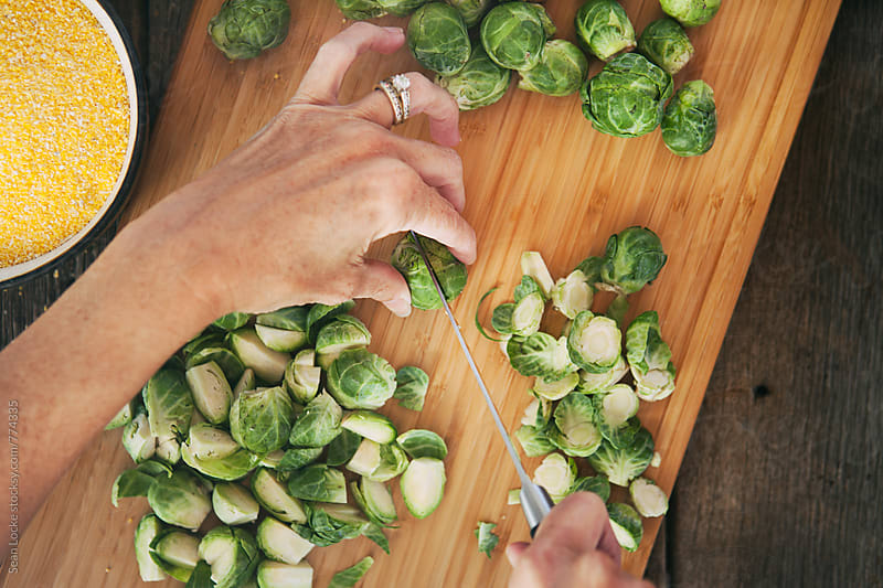 Polenta: Overhead View Of Woman Cutting Brussels Sprouts by Sean Locke for Stocksy United