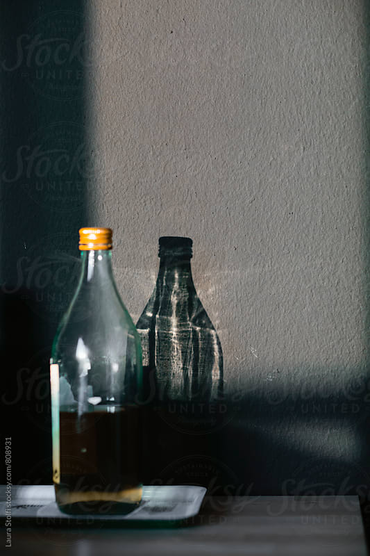 Olive oil bottle and its shadow with sunrays on it by Laura Stolfi for Stocksy United