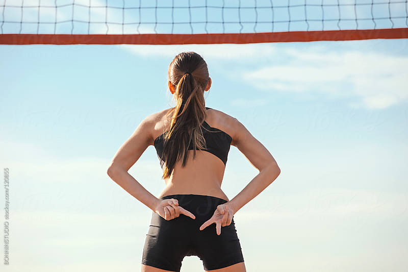 Beach volleyball. Sporty woman showing sign to teammates. by BONNINSTUDIO for Stocksy United