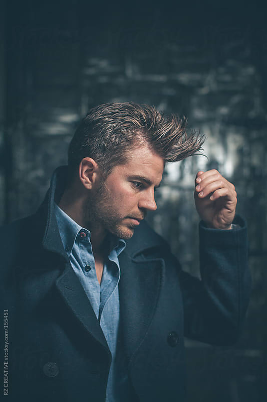 Portrait of a man wearing a peacoat and fixing his hair. by RZ CREATIVE for Stocksy United