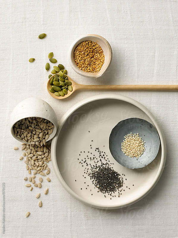 seeds and nuts in small bowls by Naoko Kakuta for Stocksy United