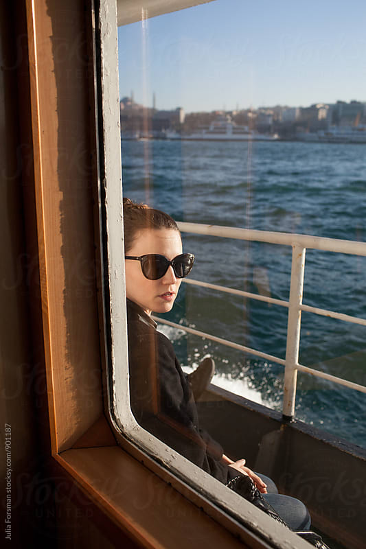 Woman wearing sunglasses seen through a ferryboat window during her commute in Istanbul. by Julia Forsman for Stocksy United