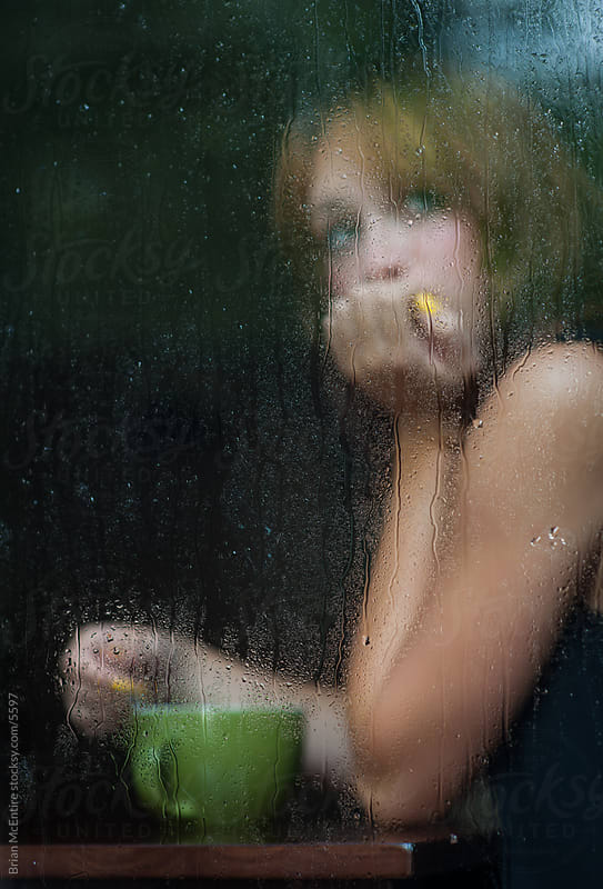 Moody scene of woman in cafe on rainy day by Brian McEntire for Stocksy United