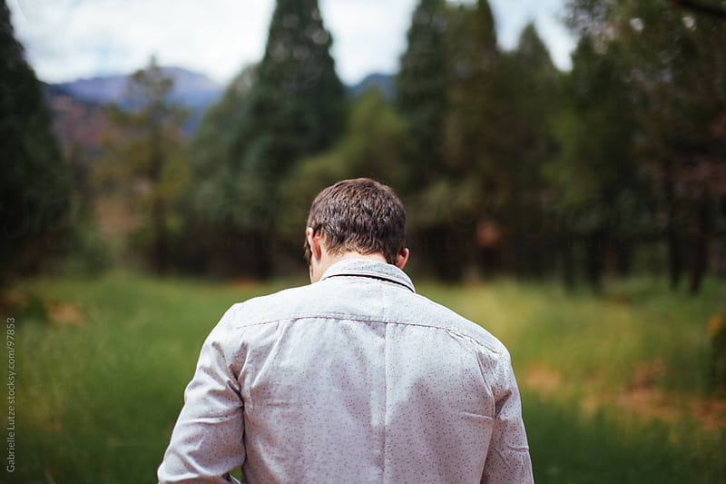 Man in field - from the back by Gabrielle Lutze for Stocksy United