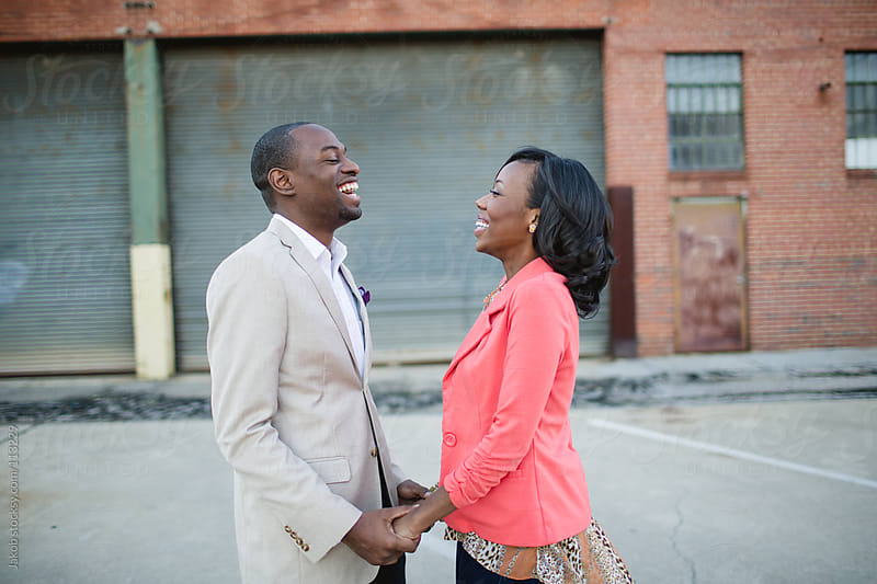 Young black couple holding hands while laughing by Jakob for Stocksy United