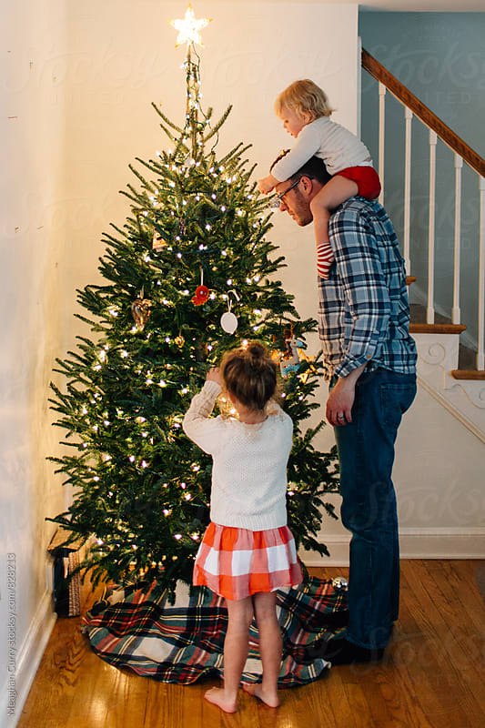 a father and his daughters decorate a Christmas tree by Meaghan Curry for Stocksy United