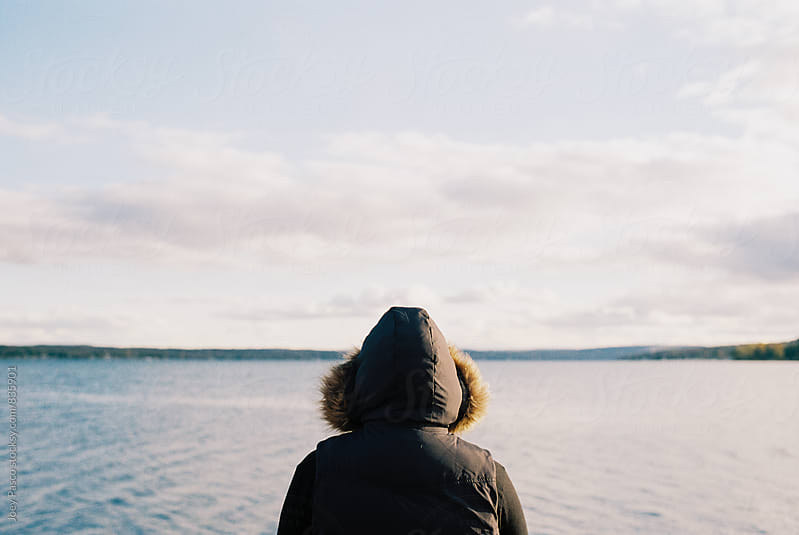 Adult in furry hooded coat looks out across a lake in chilly weather by Joey Pasco for Stocksy United
