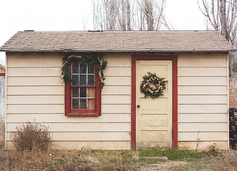 An old shed decorated with holiday swag and wreath by Tana Teel for Stocksy United