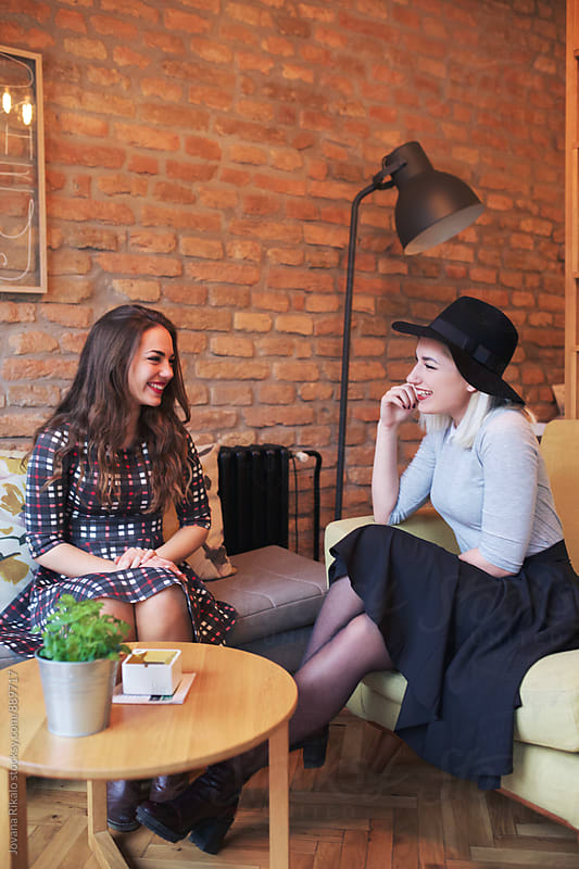Two female friends sitting and talking in a cafe shop by Jovana Rikalo for Stocksy United
