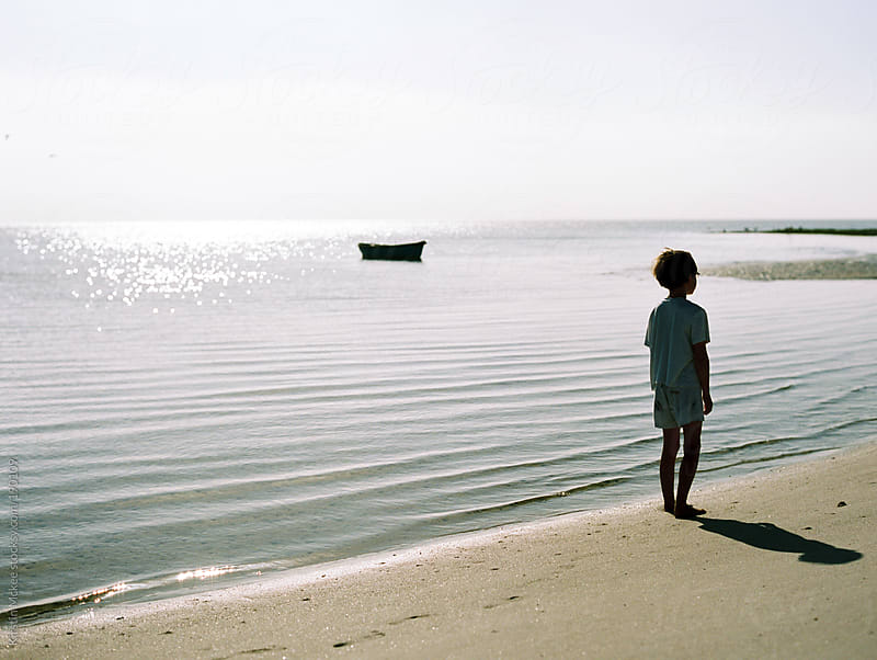 Boy standing on deserted beach.  by Kirstin Mckee for Stocksy United