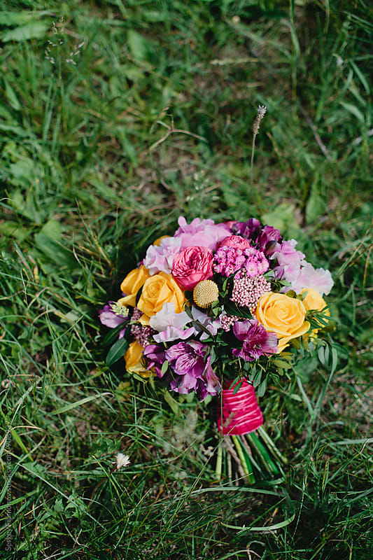 Bridal bouquet lying on the green grass by Sergey Filimonov for Stocksy United