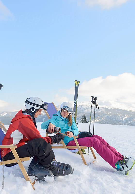 Friends drinking tea in lounge chair on the ski slope by RG&B Images for Stocksy United