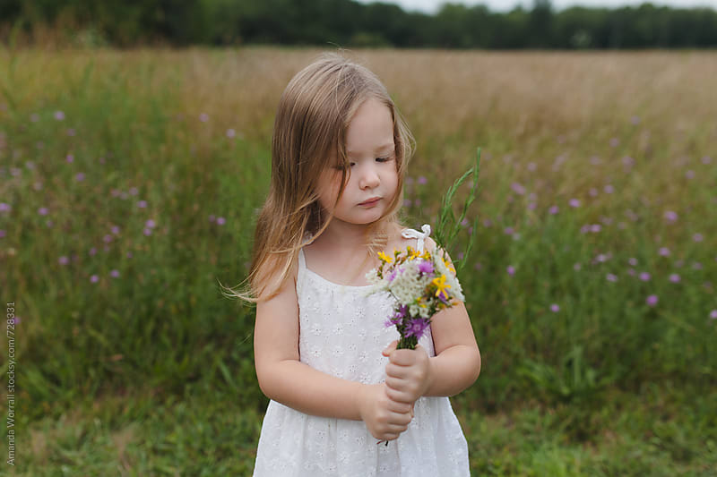 Young girl standing in a field holding a bouquet of wildflowers by Amanda Worrall for Stocksy United