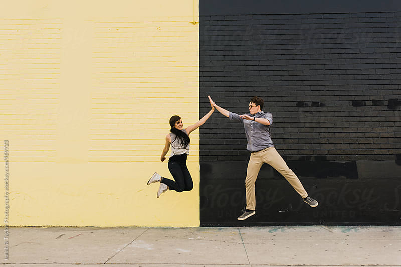 Happy friends jumping and high-fiving by Isaiah & Taylor Photography for Stocksy United