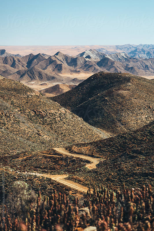 Scenic mountainous desert landscape with road leading into the distance by Micky Wiswedel for Stocksy United