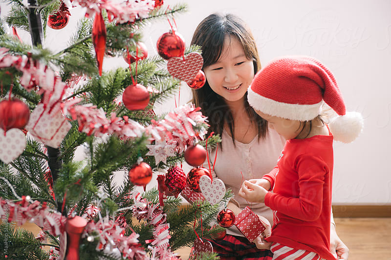 A cute toddler girl  and her mother decorating christmas tree by Maa Hoo for Stocksy United