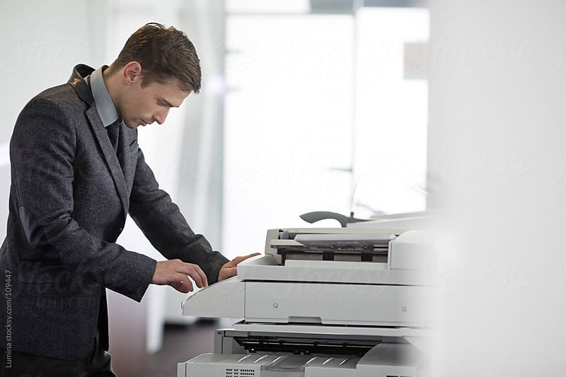 Businessman Using a Copier by Lumina for Stocksy United