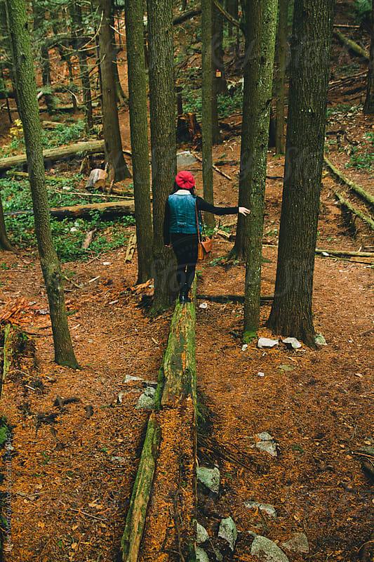 woman walking down fallen log in woods by Jesse Morrow for Stocksy United