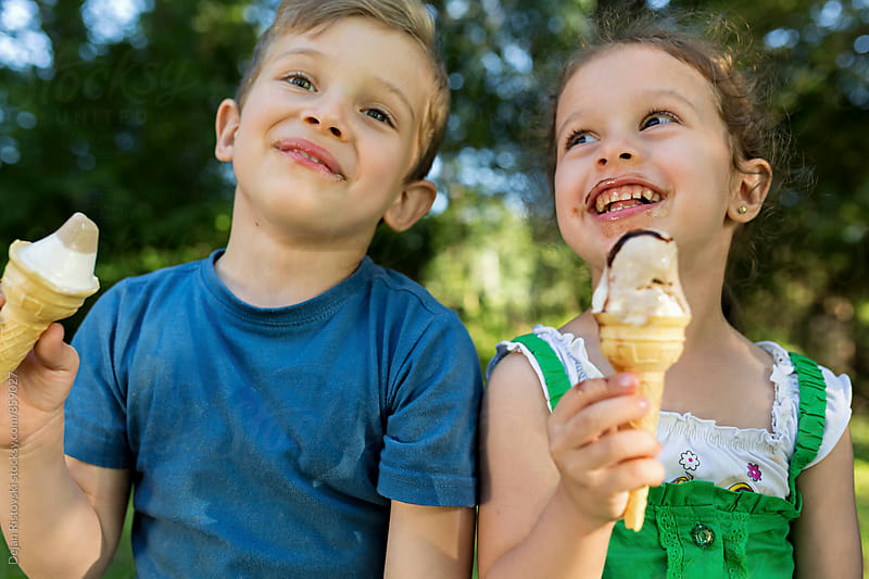 Siblings eating ice cream. by Dejan Ristovski for Stocksy United