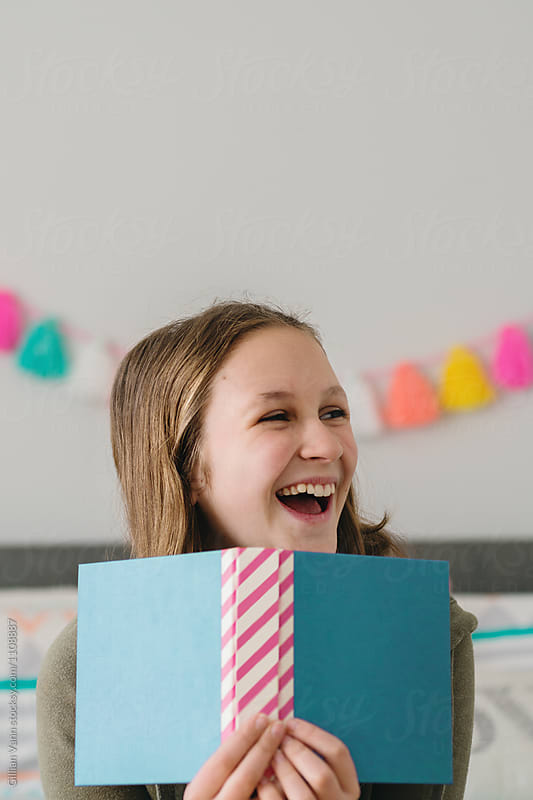 teen girl laughing behind a book with blank cover, blues and pin