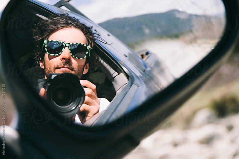 Young man taking a selfie with a dslr on a truck driving mirror by Alejandro Moreno de Carlos for Stocksy United