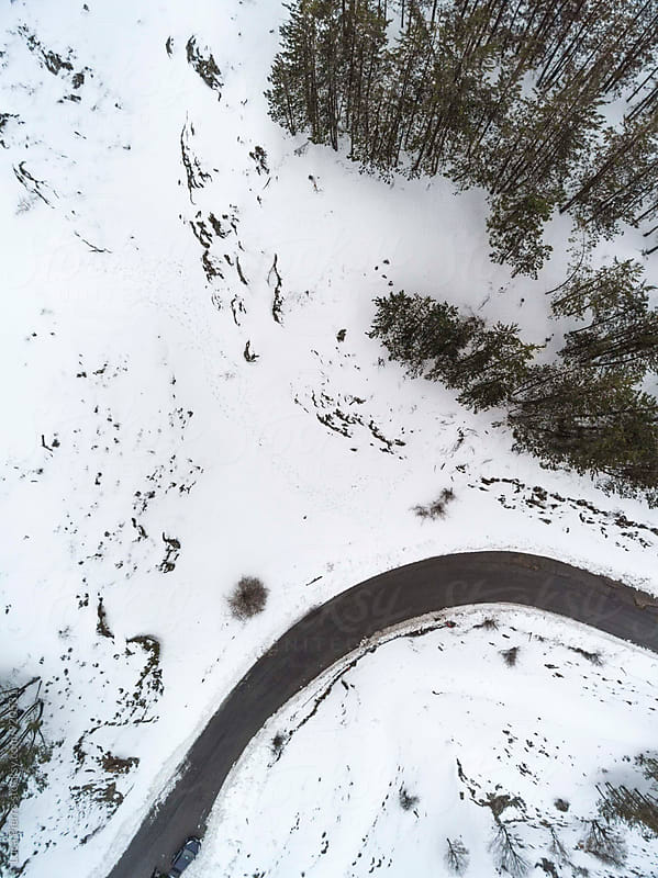 Aerial view of a forest and road under the snow by Luca Pierro for Stocksy United