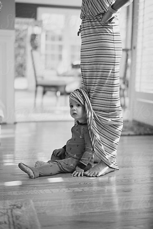 Cute young boy hiding under his mother's dress by Jakob for Stocksy United
