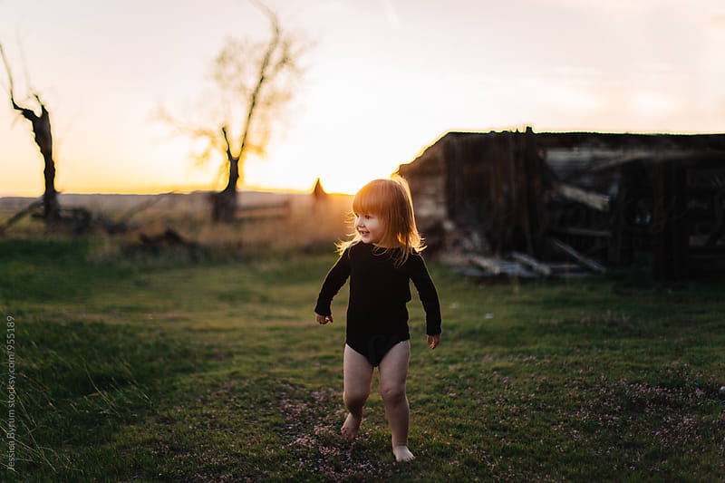 Toddler girl playing in field at sunset by Jessica Byrum for Stocksy United