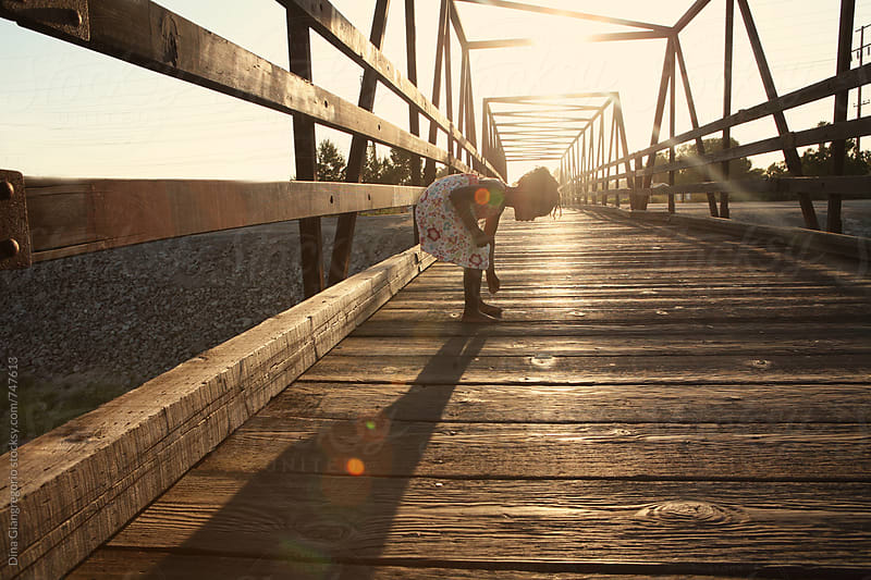 African American Girl On Wooden Bridge Bending Down by Dina Giangregorio for Stocksy United