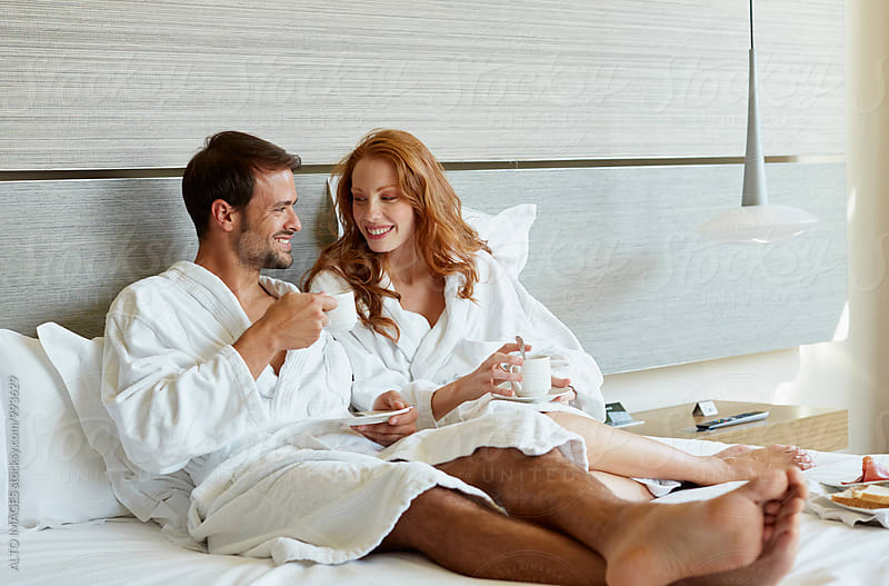 Couple Wearing Bathrobes While Having Coffee In Bed by ALTO IMAGES for Stocksy United