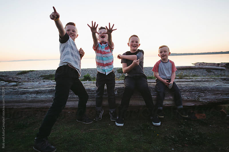 Excited young boys having fun together outside near ocean by Rob and Julia Campbell for Stocksy United