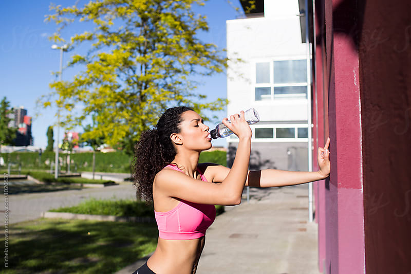 Fit woman drinking water by michela ravasio for Stocksy United