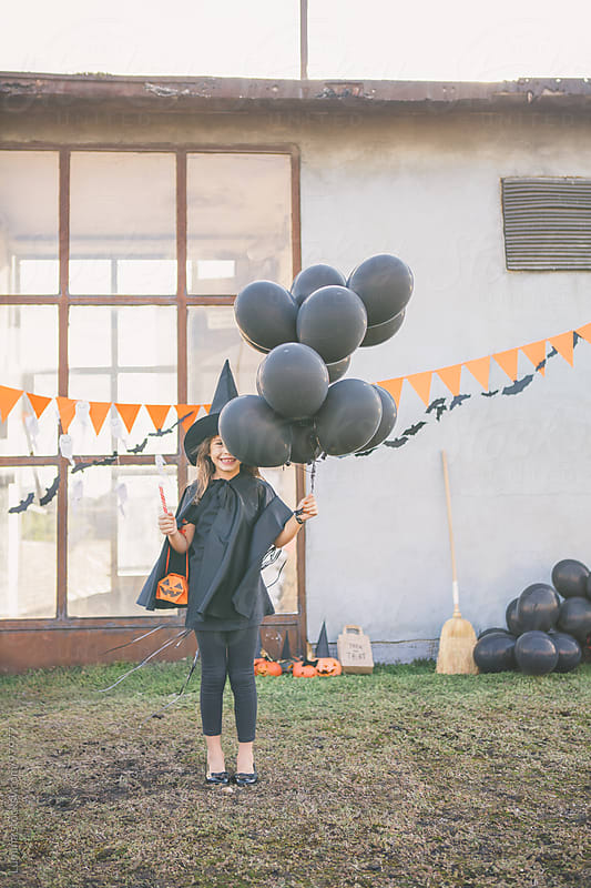 Halloween Witch Holding Black Balloons by Lumina for Stocksy United