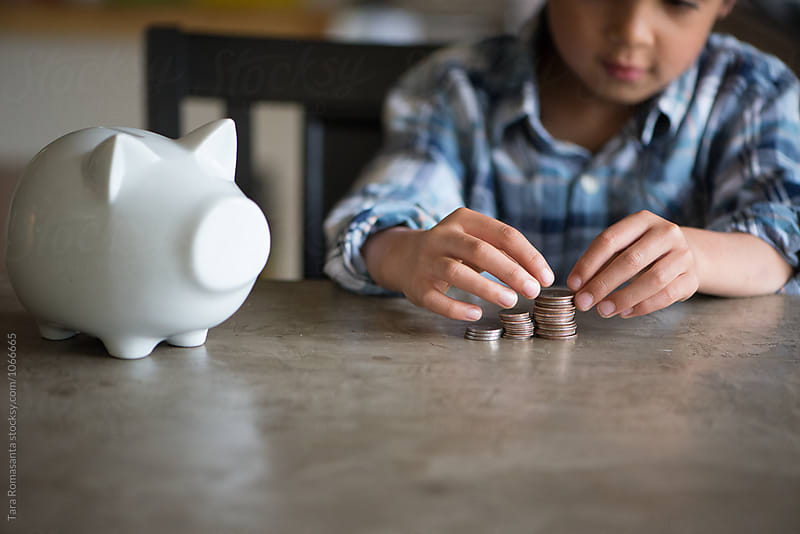 boy counts a stack of coins by Tara Romasanta for Stocksy United