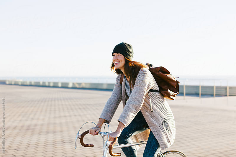 Smiling woman riding her vintage bicycle in the city. by BONNINSTUDIO for Stocksy United