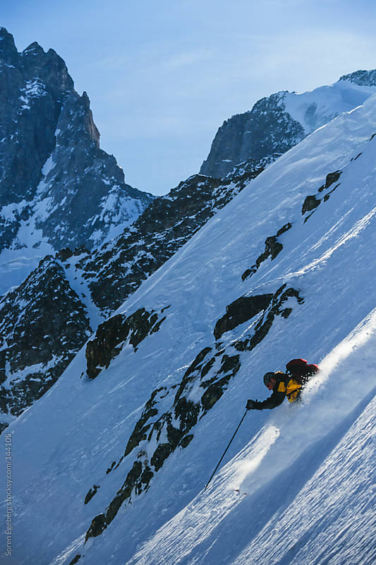 Man skiing steep powder snow in winter mountain landscape. by Soren Egeberg for Stocksy United