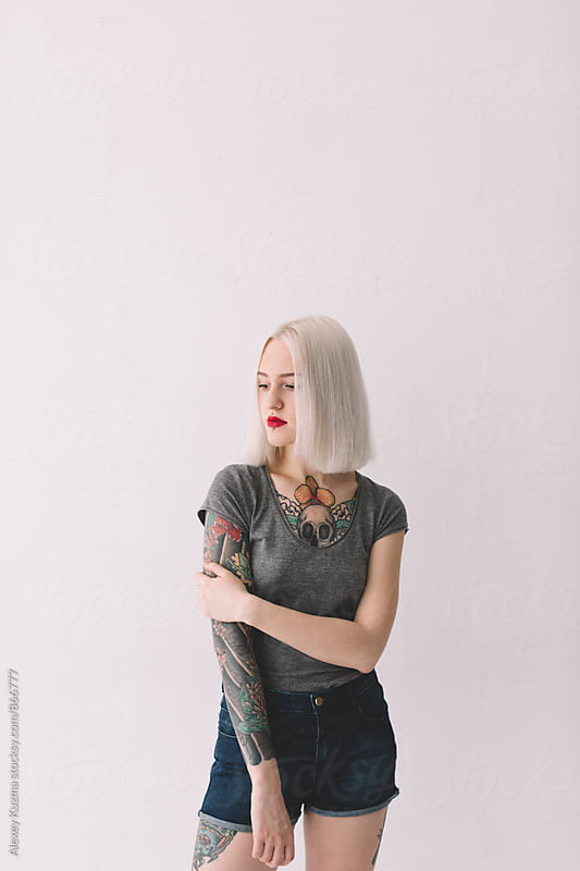 young blond woman with tattoos on the white background  by Vesna for Stocksy United