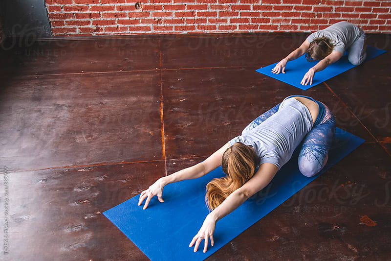 Man and woman stretching while sitting on rugs in yoga studio by Danil Nevsky for Stocksy United
