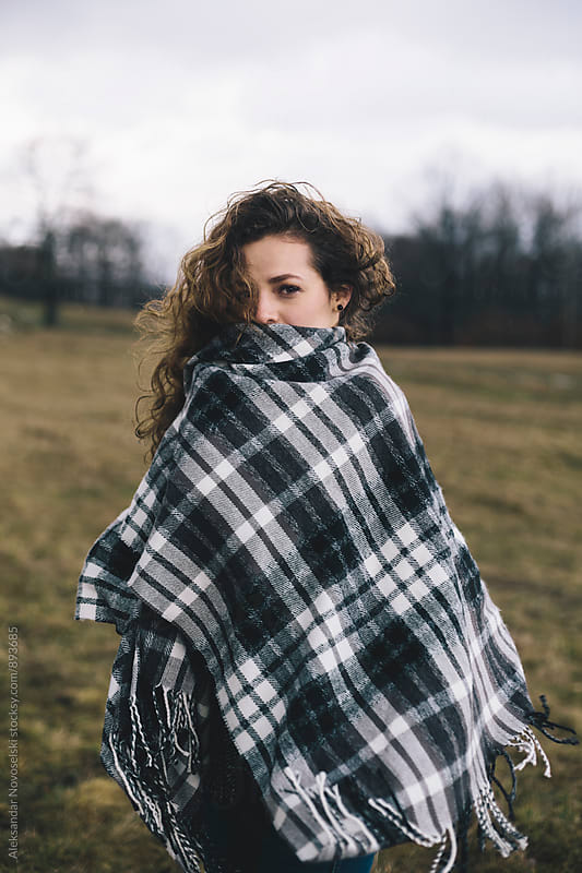 Portrait of young woman wearing a poncho, outdoors by Aleksandar Novoselski for Stocksy United