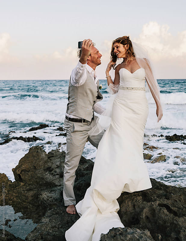 New Married couple taking a selfie on the ocean by Shaun Robinson for Stocksy United