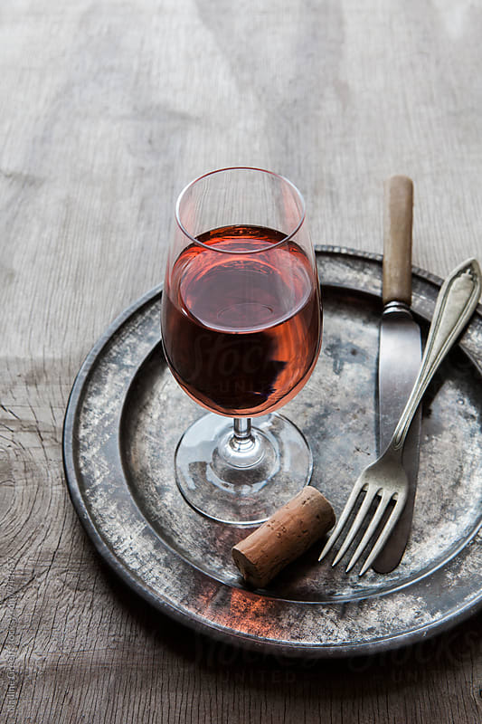 Glass of rose wine with plate, fork and knife by Nadine Greeff for Stocksy United