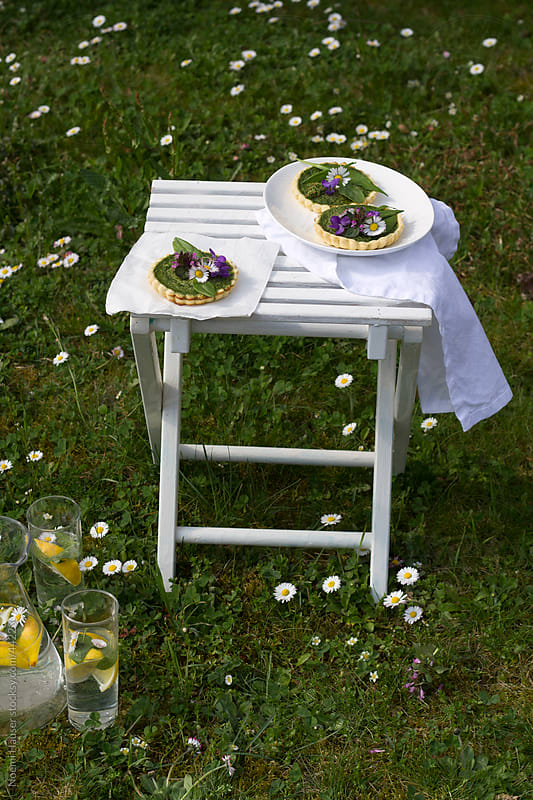 Spinach quiche with spring flowers on white chair by Noemi Hauser for Stocksy United