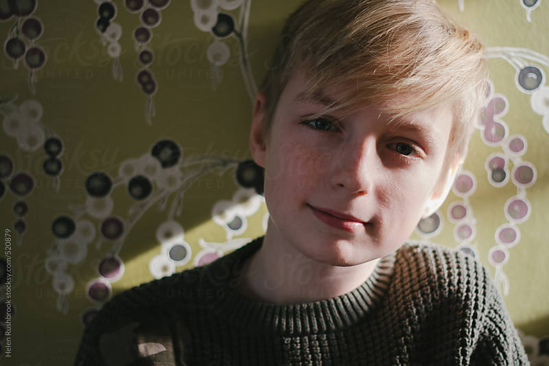 A pre-teen boy looking at camera with a half-smile. by Helen Rushbrook for Stocksy United