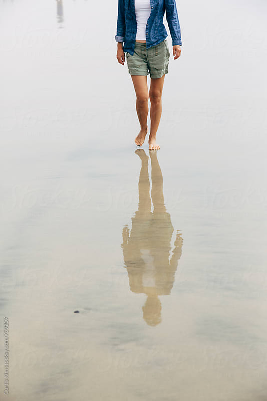 Woman walking on the beach early morning by Curtis Kim for Stocksy United